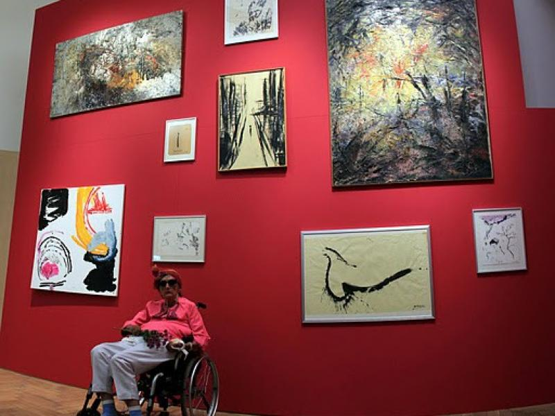Soshana in front of her paintings